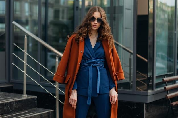 따뜻한 갈색 코트와 파란색 정장, 봄 가을 유행 패션 거리 스타일을 입고 도시의 도시 비즈니스 거리에서 걷고 매력적인 세련된 여자, 선글라스를 착용