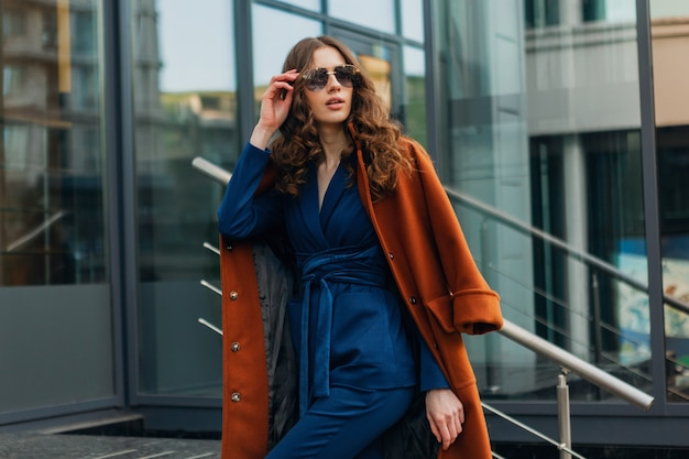 Attractive stylish woman with walking in urban city business street dressed in warm brown coat and blue suit, spring autumn trendy fashion street style, wearing sunglasses