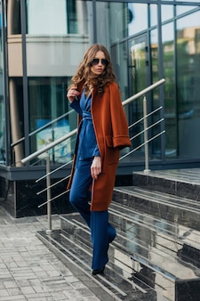 Attraente donna elegante con passeggiate in strada di affari della città urbana vestita di caldo cappotto marrone e abito blu, stile di strada moda alla moda primavera autunno, indossando occhiali da sole