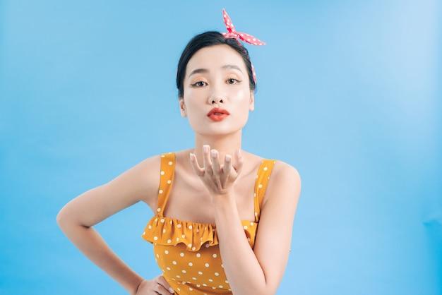 Привлекательная стильная молодая женщина в ретро-желтом платье в горошек с открытыми ладонями, надутыми губами и воздушными поцелуями