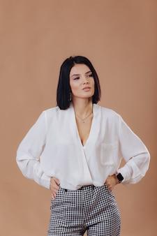 Ragazza alla moda attraente in abbigliamento di affari che posa sulla parete crema. concetto di abiti eleganti e raffinatezza.