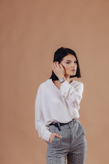 Привлекательная стильная молодая девушка в деловой костюм позирует на фоне крем. концепция стильной одежды и изысканности.