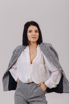 Привлекательная стильная молодая девушка в деловой одежде позирует на светлом фоне в студии. концепция стильной одежды и изысканности.