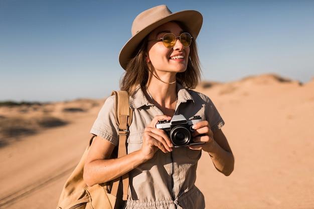 Привлекательная стильная молодая женщина в платье цвета хаки в пустыне, путешествующая по африке на сафари, в шляпе и рюкзаке, делающая фото на старинную камеру