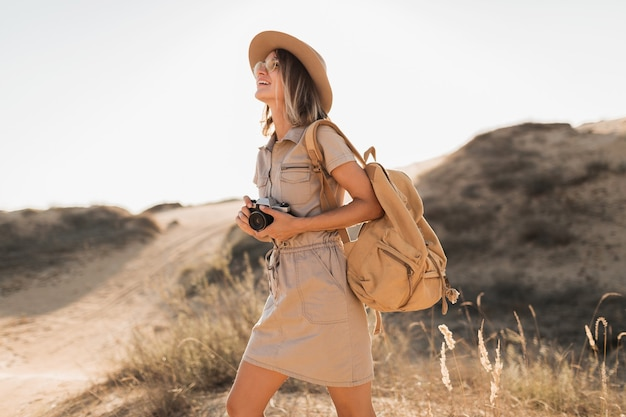 Attractive stylish young woman in khaki dress in desert, traveling in africa on safari, wearing hat and backpack, taking photo on vintage camera
