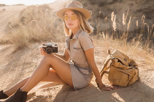 Attraente giovane donna elegante in abito color cachi nel deserto, viaggiando in africa in safari, indossando cappello e zaino, prendendo foto con la macchina fotografica d'epoca