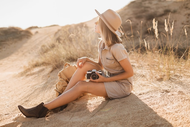 Attractive stylish young woman in khaki dress in desert, traveling in africa on safari, wearing hat and backpack