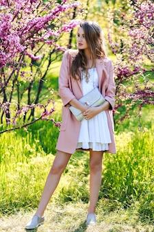 Attraente giovane donna elegante in abito bianco chiaro, cappotto rosa, con i capelli lunghi che cammina nel giardino con fioritura sakura
