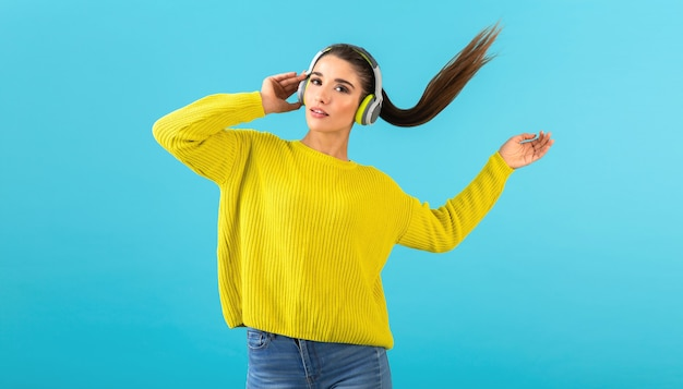 Attractive stylish young woman listening to music in wireless headphones happy wearing yellow knitted sweater colorful style fashion posing isolated on blue background waving long hair tail