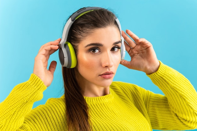 Attractive stylish young woman listening to music in wireless headphones happy wearing yellow knitted sweater colorful style fashion posing isolated on blue background