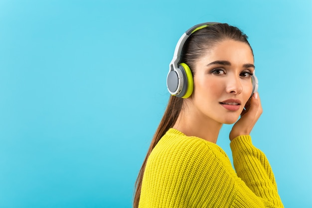 Attractive stylish young woman listening to music in wireless headphones happy wearing yellow knitted sweater colorful style fashion posing isolated on blue wall
