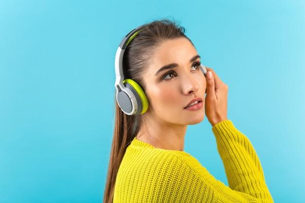 Привлекательная стильная молодая женщина, слушающая музыку в беспроводных наушниках, счастлива носить желтый вязаный свитер красочный стиль моды позирует изолирована на синей стене
