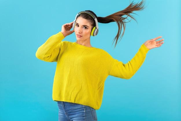 ワイヤレス ヘッドフォンで音楽を聴く魅力的なスタイリッシュな若い女性が黄色のニット セーター カラフルなスタイルのファッション ポーズを着て幸せ