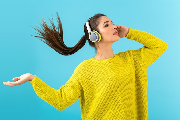 Привлекательная стильная молодая женщина, слушающая музыку в беспроводных наушниках, счастлива носить желтый вязаный свитер