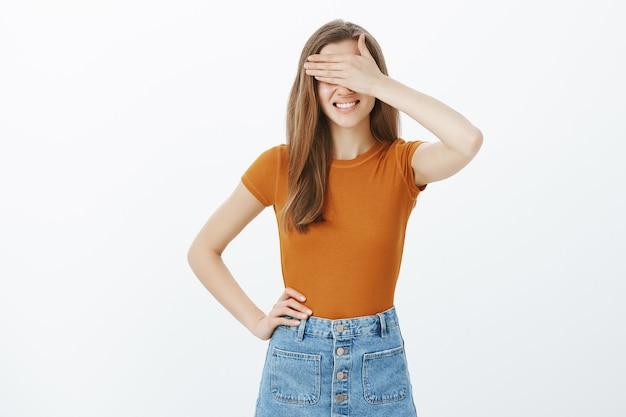Attraente giovane donna alla moda in attesa di sorpresa, coprire gli occhi e sorridere, anticipando