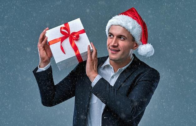 회색 배경에 스튜디오에서 선물 상자와 산타 클로스 모자에 재킷과 셔츠에 매력적인 성공적인 사업가.