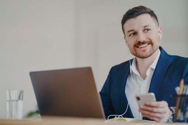 ノートパソコンの前にイヤフォンを付け、携帯電話を持ちながらオンライン会議に参加する、魅力的な成功した男性ビジネスマン、オフィスの机の後ろに座るスタイリッシュなスーツのマネージャー