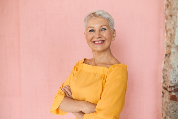 Attraente imprenditrice bionda di mezza età di successo con capelli corti da folletto e affascinante sorriso sicuro in posa isolato su sfondo muro rosa vuoto, mantenendo le braccia incrociate sul petto
