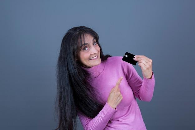 백인 외모의 매력적인 성공적인 여성, 신용 카드를 보여주는 장발 갈색 머리.