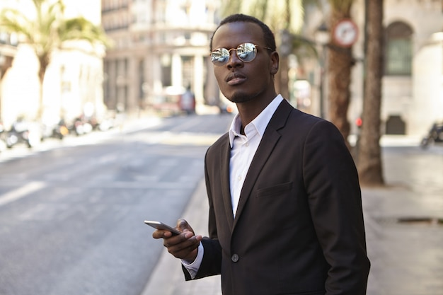Attractive successful young african american entrepreneur wearing black formal suit and mirrored lens sunglasses standing on street with smartphone, hailing up taxi, looking ahead with impatience