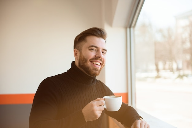 Attractive successful young businessman drinking coffee sitting at cafe table.