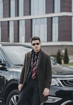 Привлекательный успешный молодой бизнесмен в деловом костюме возле своей машины