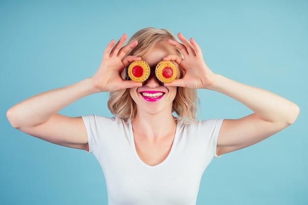 Привлекательная удивленная и пораженная женщина блондинка с макияжем и помадой на губах цвета фуксии улыбается держит калорийное печенье в студии на синем фоне