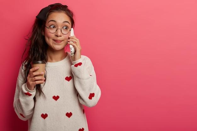 매력적인 놀란 아시아 십대는 핸드폰을 통해 이야기하고, 소문을 듣고, 테이크 아웃 커피를 마시고, 긴 포니 테일을 가지고 있습니다.