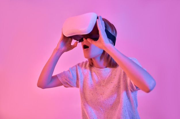 Attractive surprised shocked woman in casual wear using virtual reality glasses isolated on neon pink