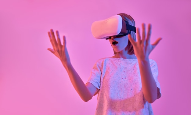 Attractive surprised shocked woman in casual wear using virtual reality glasses looks at her hands isolated on neon pink