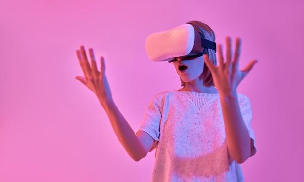 가상 현실 안경을 사용하여 캐주얼웨어에 매력적인 놀란 충격을받은 여자는 네온 핑크에 고립 된 그녀의 손을 본다