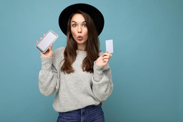 검은 모자와 회색 스웨터를 입은 매력적인 젊은 브루네트 여성이 신용카드와 휴대전화를 들고 카메라를 쳐다보는 흉내내기용 빈 디스플레이를 들고 파란색 배경 위에 격리되어 있습니다.