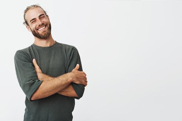 Привлекательный мужчина со стильными волосами и бородой смеется со скрещенными руками и закрытыми глазами.