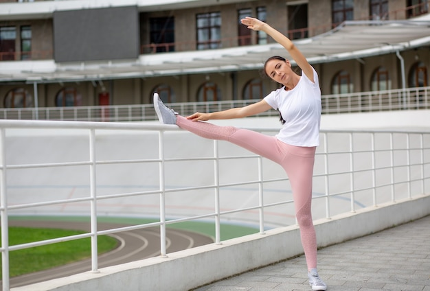 Attractive tanned sporty woman stretching before running leaning her leg on barrier. space for text