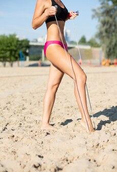 ビーチで縄跳びでストレッチをしている完璧なボディを持つ魅力的な日焼けした女性