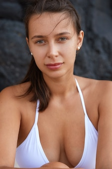 Attractive tanned young female tourist model wears white swimwear