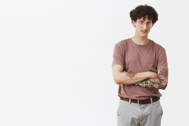 Привлекательный татуированный мужчина, который сильно подозревает, что парень хочет обмануть его, скрестив руки на груди, хмурясь, серьезно и озабоченно смотрит, стоит в очках и в стильной городской одежде