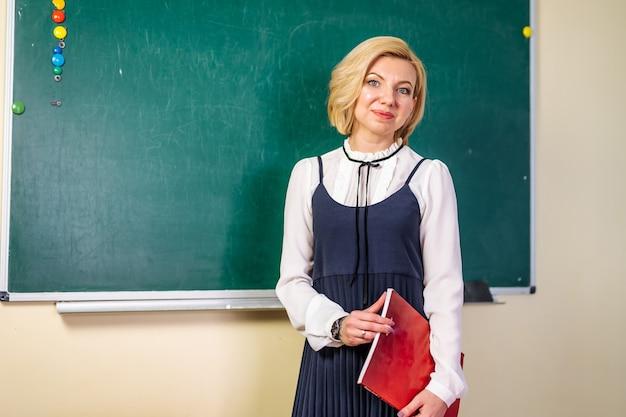 黒板の魅力的な先生。学校に戻る。教育。教室の先生。