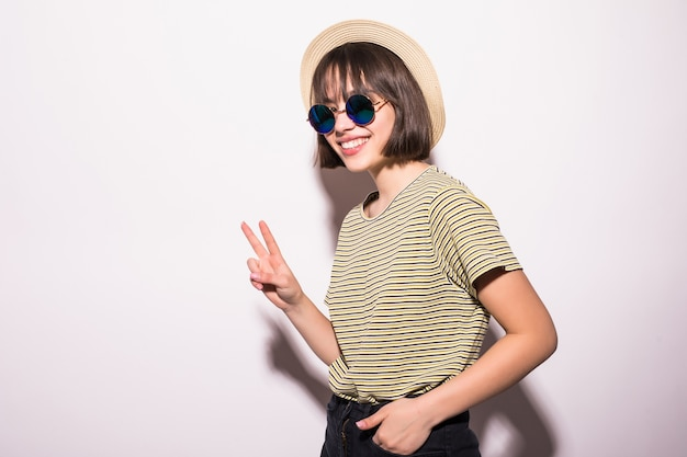 Attractive teen hipster girl in hat, sunglasses isolated