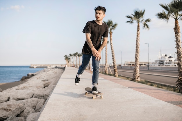 Attractive teenage boy skateboarding near the coast