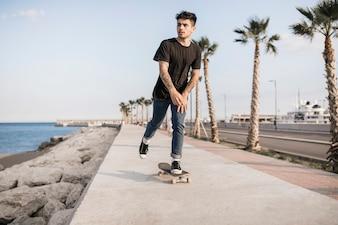 Attractive teenage boy skateboarding near the coast