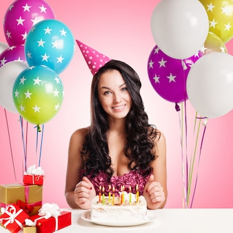 Attractive teenage girl celebrating her birthday with cake