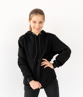 白い背景で隔離の黒いパーカーでポーズをとって魅力的な10代の少女