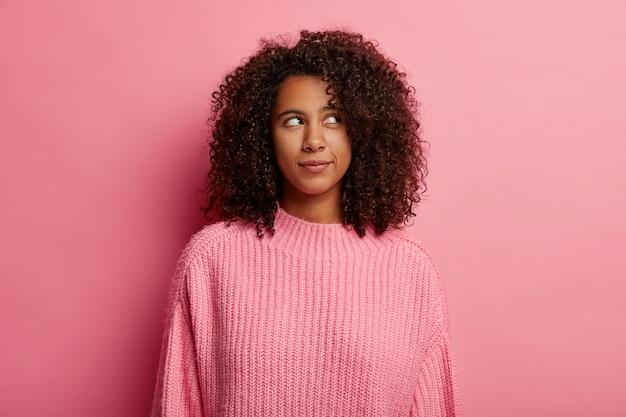 Attraente ragazza adolescente con i capelli afro guarda pensierosa nell'angolo in alto a destra, ha un'espressione pensierosa, vestita con un maglione rosa, posa al coperto, dubbi su qualcosa.
