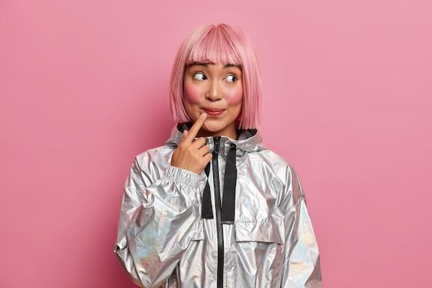 Attraente ragazza adolescente con acconciatura rosa alla moda, tiene il dito indice vicino alle labbra, sembra curiosamente da parte vestita con un cappotto d'argento alla moda