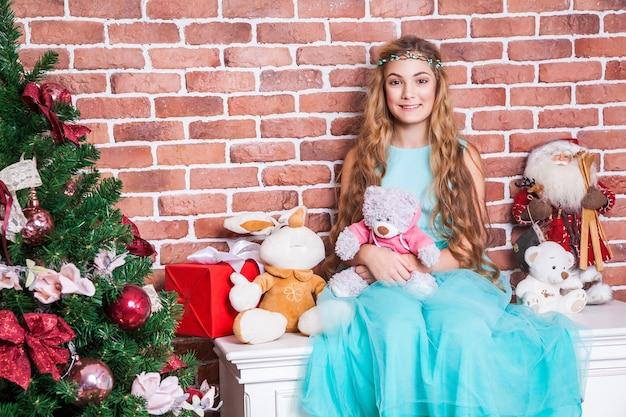 매력적인 10대 장발 금발은 크리스마스 트리 근처의 흰색 탁자에 앉아 이빨 미소를 짓고 카메라를 바라보고 있습니다. 스튜디오 촬영