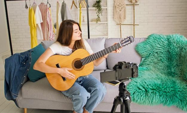 ギターで遊んでいる間vlogging魅力的なティーンエイジャーの女の子。彼女のビデオブログを撮影しながらギターで話したり遊んだりする魅力的な若い女の子。音楽について話している若いかなりvlogger。