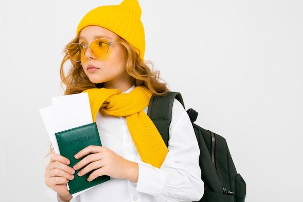Привлекательная девушка подросток с рюкзаком, шарф, шляпа и паспорт с билетами на белой студии
