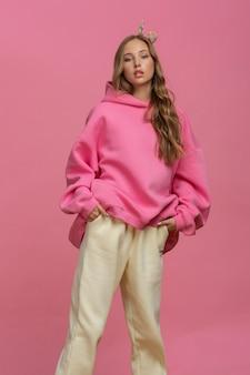 ピンクの背景にカラフルなスポーツウェアでポーズをとる魅力的なティーンエイジャーの長髪のファッショニスタ
