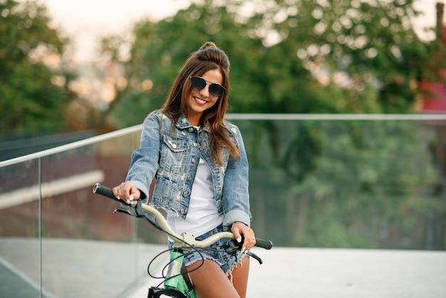 Привлекательная заманчивая молодая девушка в модной джинсовой одежде носит стильные очки, сидит на велосипеде и позирует на камеру в летний вечер.